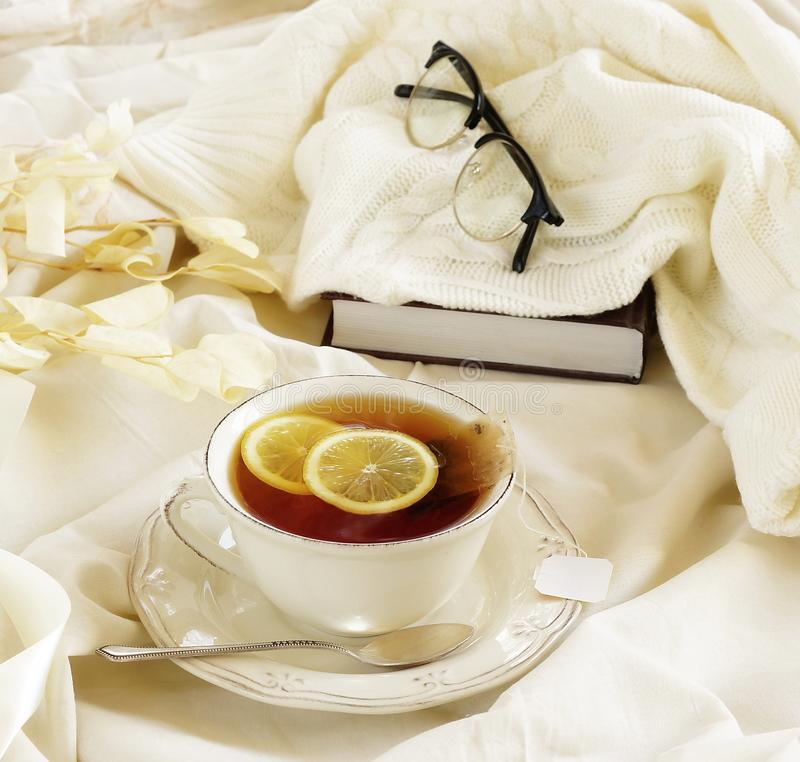 .warm beige pastel colors lifestyle autumn winter composition. Tea with lemon, knitted sweater , glasses and book. home workspace in bed concept.warm beige royalty free stock photography