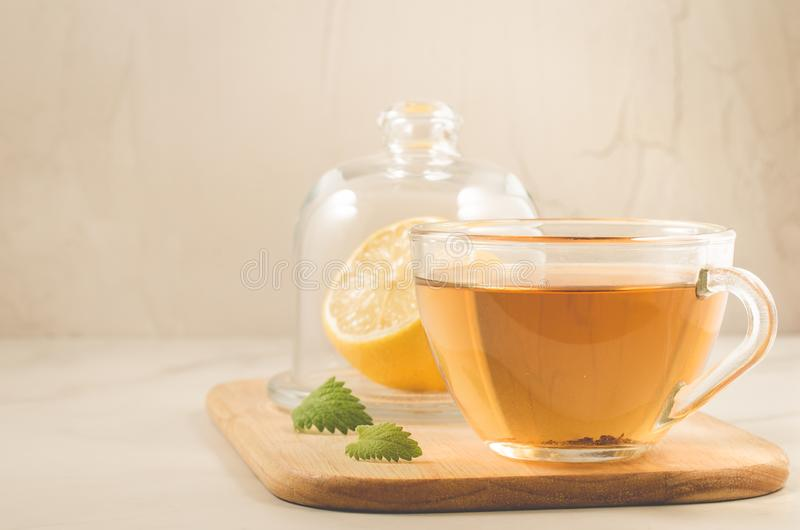Tea with a lemon and mint/tea with a lemon and mint on a wooden tray on a white stone background. Selective focus and copyspace royalty free stock images