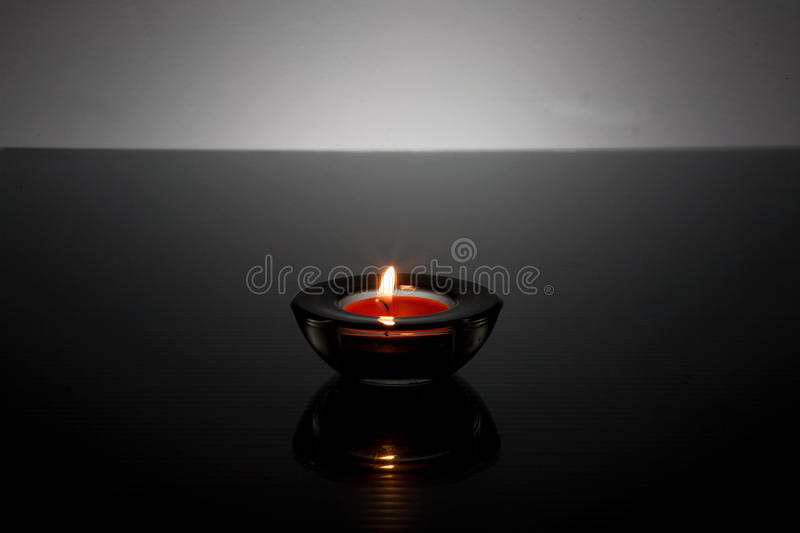 Tea light Candle in glass holder. On a black frosted glass tabletop with a white background stock images