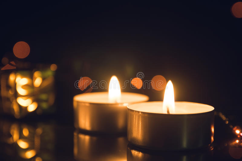 Tea Light Candles burning with bokeh lights on black background stock photography