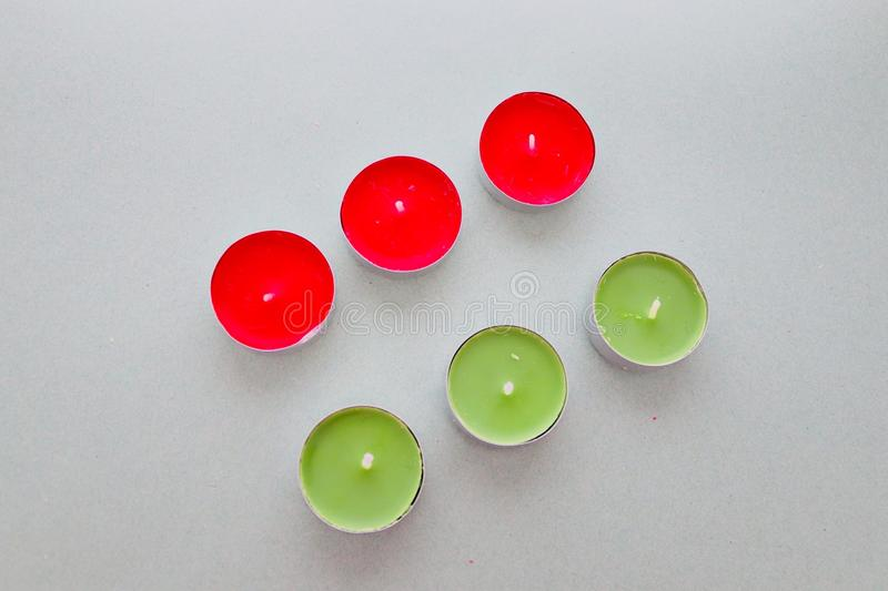 Tea lights on a plain grey background.red and green candles royalty free stock photography
