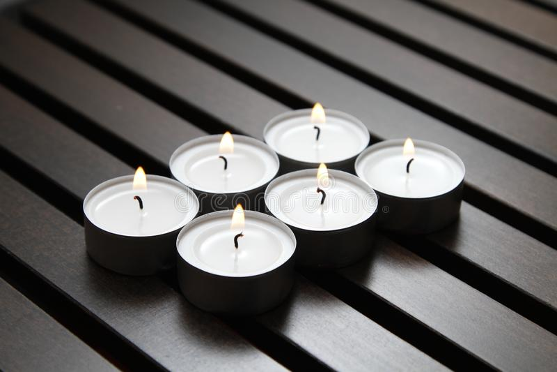 Tea lights. Burning tea lights on a wooden bench stock photos
