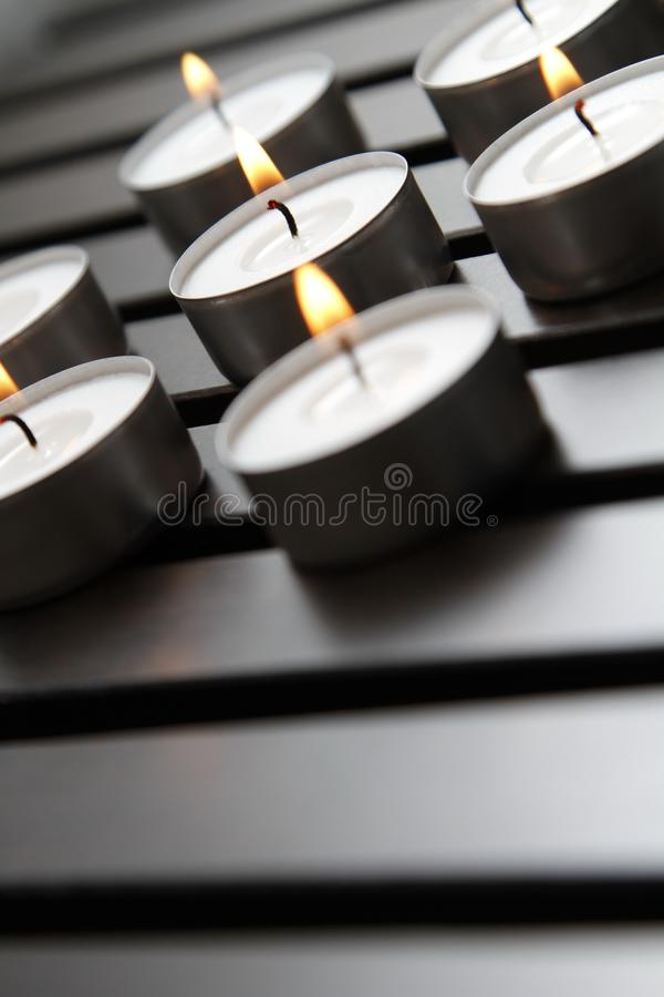 Tea lights. Burning tea lights on a wooden bench royalty free stock images