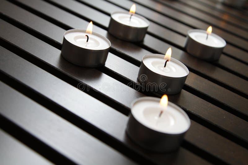 Tea lights. Burning tea lights on a wooden bench royalty free stock image