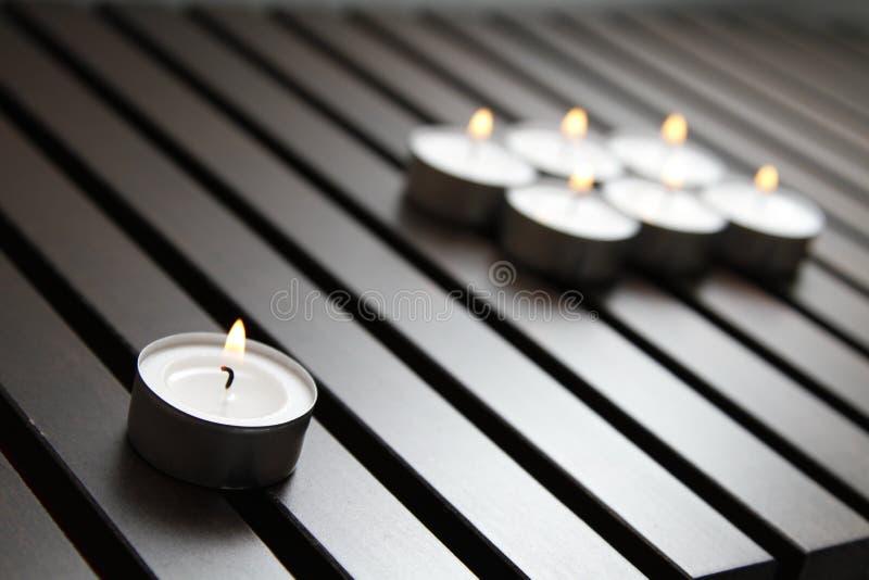 Tea lights. Burning tea lights on a wooden bench stock photo