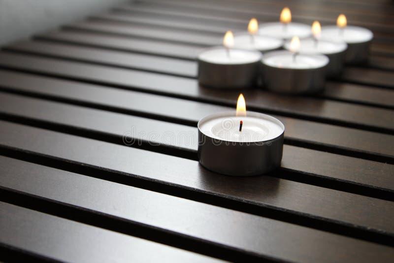 Tea lights. Burning tea lights on a wooden bench royalty free stock photo