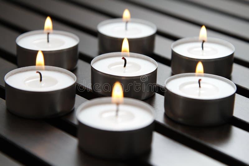Tea lights. Burning tea lights on a wooden bench stock image