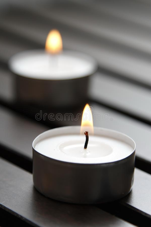 Tea lights. Burning tea lights on a wooden bench stock photography