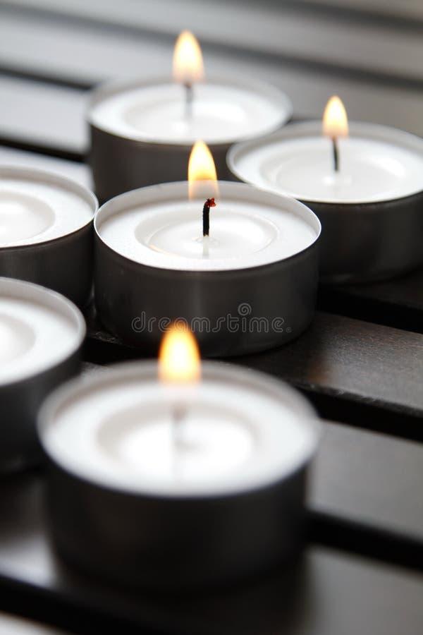 Tea lights. Burning tea lights on a wooden bench stock images