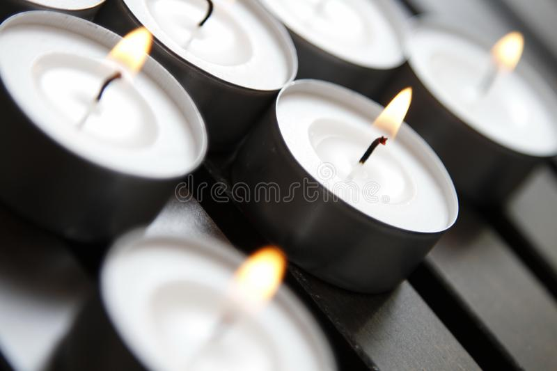 Tea lights. Burning tea lights on a wooden bench royalty free stock photography