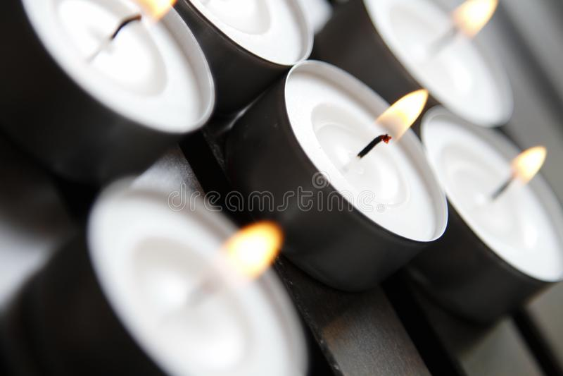 Tea lights. Burning tea lights on a wooden bench royalty free stock photos