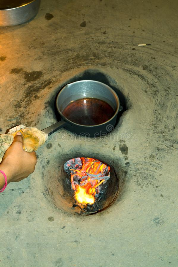 Tea making on pan using wood fired oven at rural village. Soil oven, Wood fire oven, home made oven,common oven in India, Tea is being made in the oven stock photography
