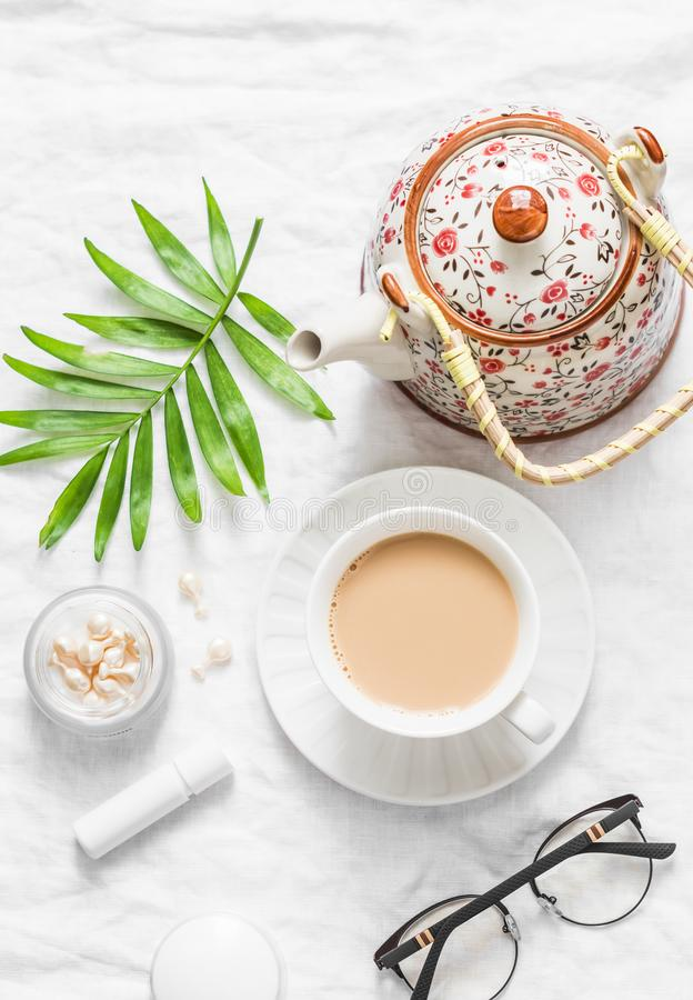 Tea with milk. Masala tea, teapot, cosmetics, lipstick, facial oil, glasses, green leaf flower on light background, top view. Cozy royalty free stock photo