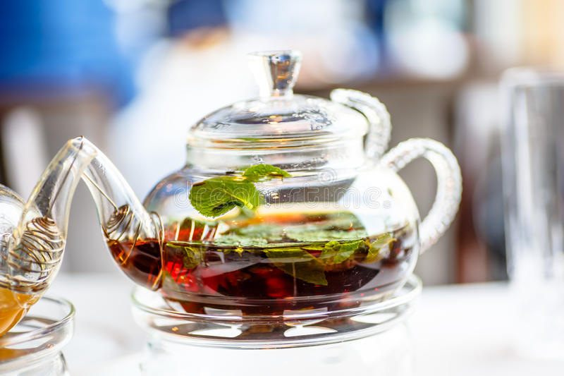 Tea with mint leaves in a glass. Teapot with a candle stock photos