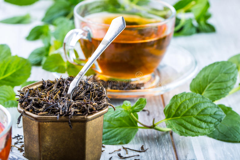 Tea. Mint Tea. Herbal tea. Mint leaf. Mint leaves. Tea in a glass cup, mint leaves, dried tea, sliced lime. herbs tea and mint lea. Ves on a slate plate in a royalty free stock images