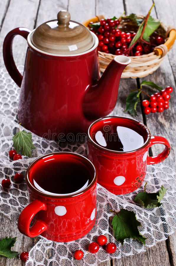 Tea in the package. Tea in ceramic mugs with berries of viburnum on a wooden surface royalty free stock photos
