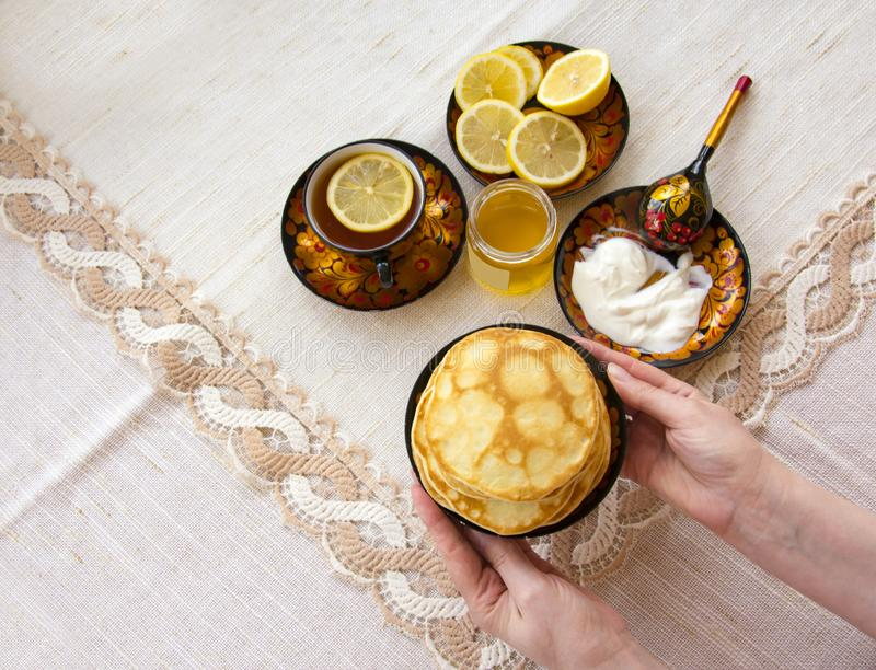 Tea in a painted Cup, on a saucer sliced lemon, pancakes, sour cream and a wooden spoon for overlaying. tea party in rustic style royalty free stock images