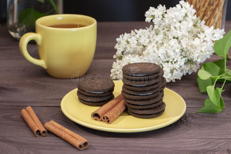 Tea pair cup and yellow saucer. Chocolate chip cookies, cinnamon sticks, white lilac on a dark wooden table. Tea ceremony, small snack, sweet dessert stock images