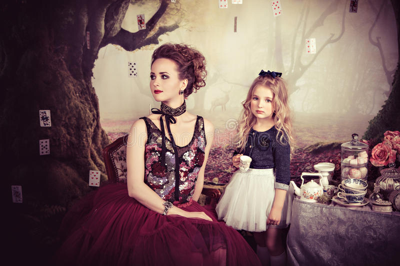 Tea party of Evil Queen and Alice in Wonderland stock photos