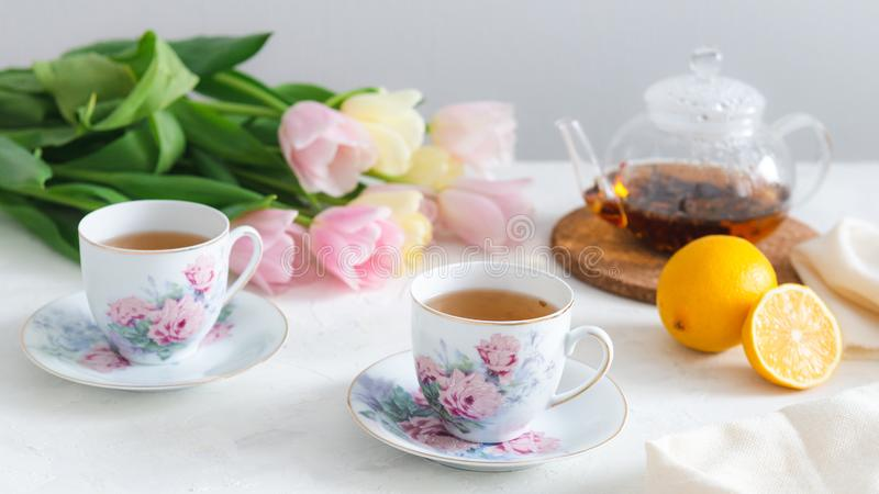 Tea party with homemade cake, lemon, teapot and tulips on the background. Spring mood, Mother`s day concept. Copy space royalty free stock photo