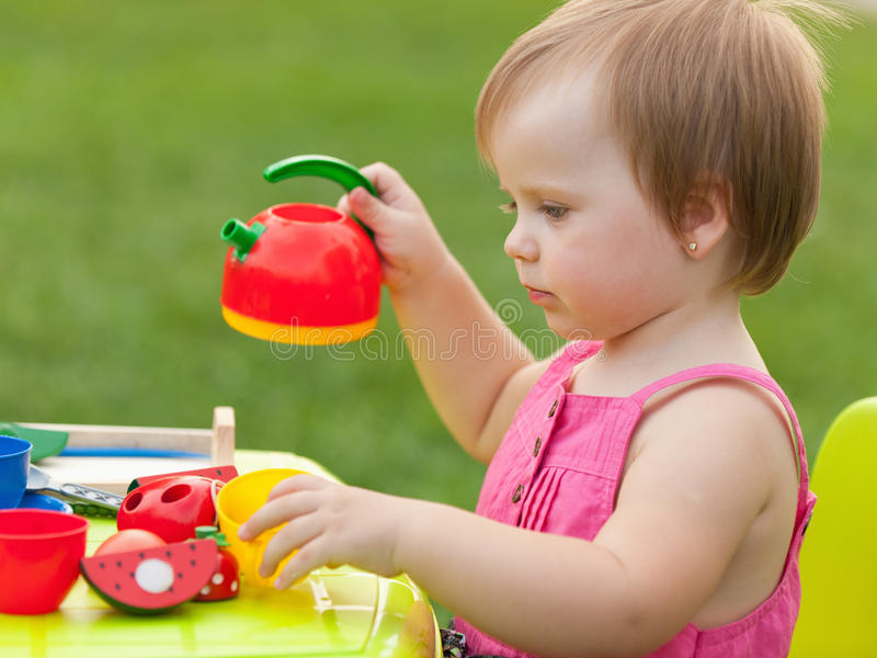 Tea party of a little girl. A little girl is playing a tea party stock photos