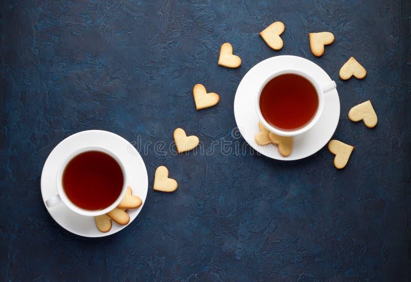 Tea party romântico para amantes no dia de Valentim O querido deu forma a cookies com os dois copos do chá no fundo de pedra imagens de stock royalty free