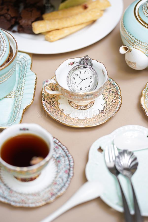 Tea party. Tea time served in the morning with different kind of. Pastries on the background. Selective focus on the vintage pocket watch stock photography
