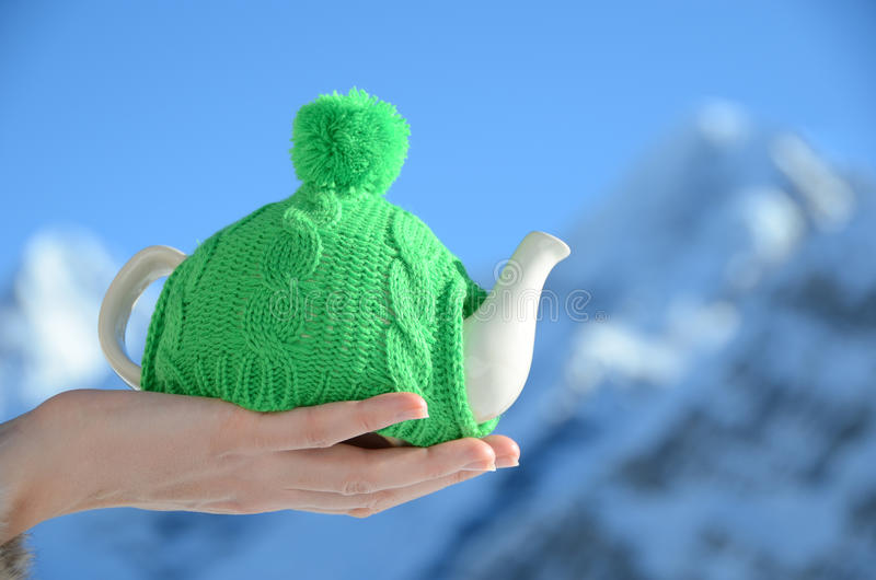 Tea pot in the knotted cap. In the hand against alpine scenery royalty free stock images