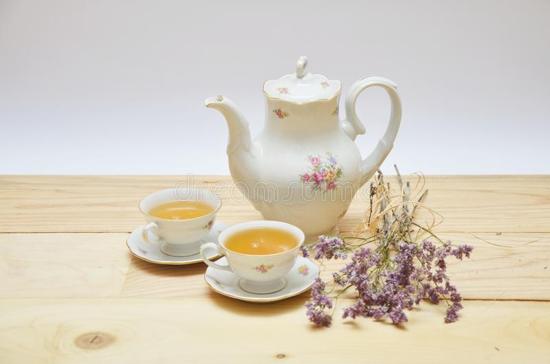 Tea pot and two cups on wooden table on white. Tea time. Relaxation, time stock image