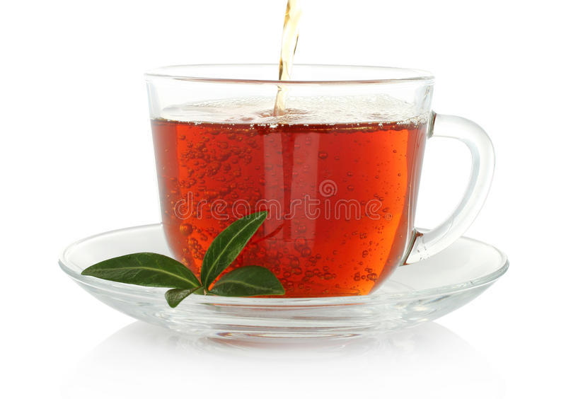 Tea pouring into cup with green leaves stock image