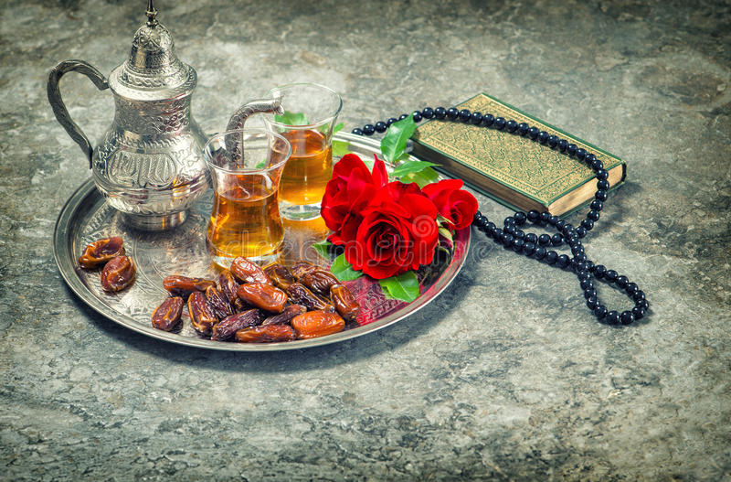 Tea and red rose flower, holy book quran and rosary. Ramadan kareem vintage stock images