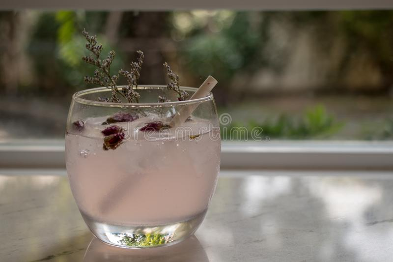 Tea with rose flower petals. Dried flower tea with ice stock photo
