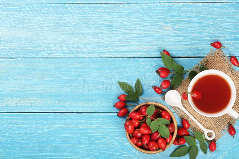 tea with rose hips and honey on white wooden background