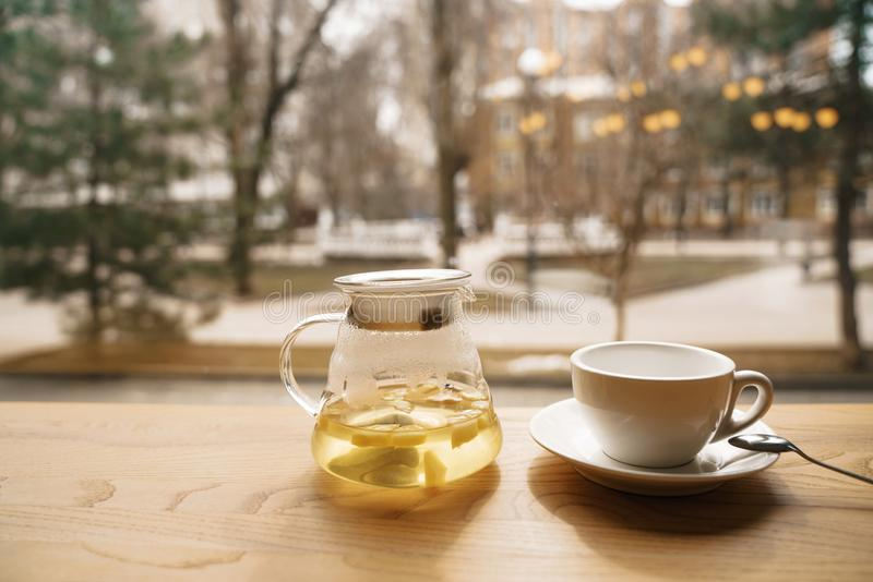 Tea from a sea-buckthorn in a transparent teapot on a wooden table on a window facing the street stock photography