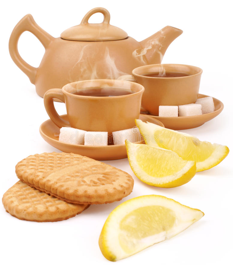 Tea set. Set of the earthenware teapot, two cups of tea, lump shugar, sliced lemon and biscuits isolated on white background with clipping path royalty free stock images