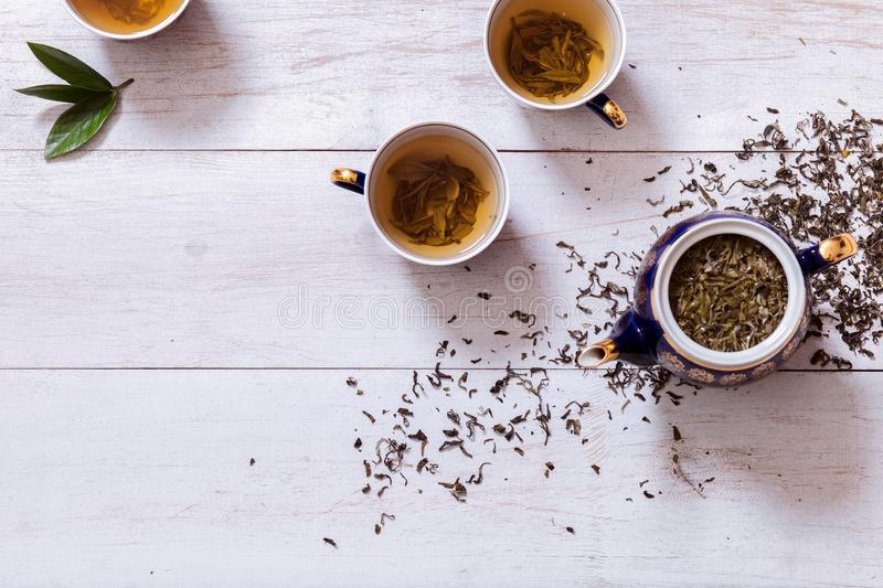 Tea set cups, teapot and brewed tea with dried leaves on white wooden table, green black herbal homemade hot beverage in porcelain royalty free stock image