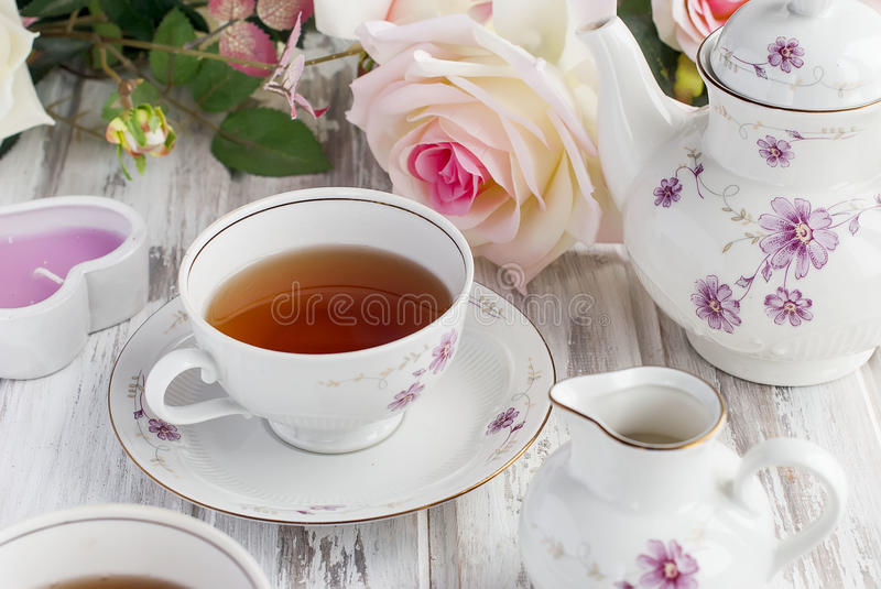 Tea set with floral print. Two teacups, teapot and milk jug, festive tableware tea service with floral pattern. holiday concept royalty free stock image