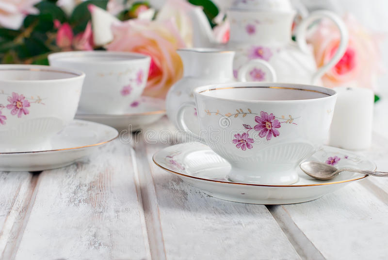 Tea set with floral print. Two teacups, teapot and milk jug, festive tableware tea service with floral pattern. holiday concept royalty free stock images