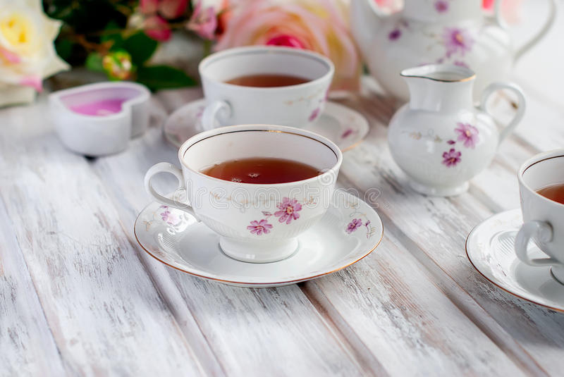 Tea set with floral print. Two teacups, teapot and milk jug, festive tableware tea service with floral pattern. holiday concept stock photography