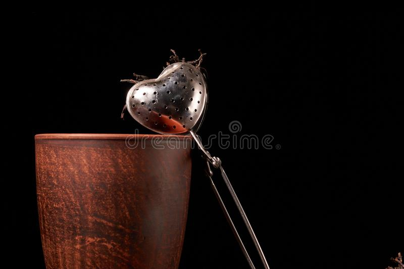 tea strainer with a cup and black tea on wooden table on dark background. Selective focus royalty free stock photo