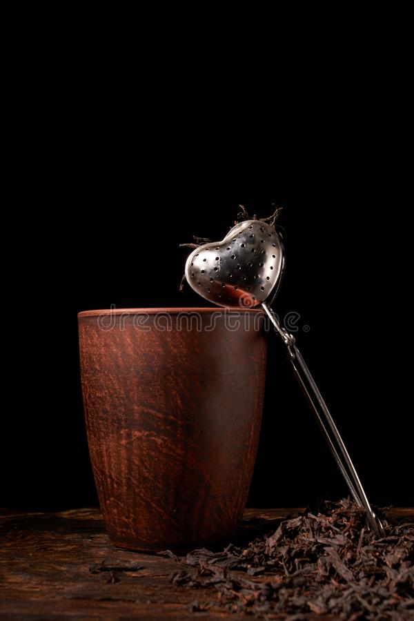 Tea strainer with a cup and black tea on wooden table on dark background. Selective focus. Tea strainer with a cup and black tea on wooden table on dark stock photography