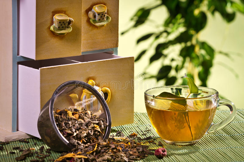 Tea Strainer and cupboard with cup stock photography