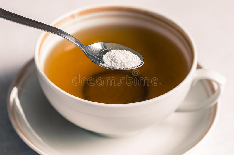 Tea with sweetener in a spoon. Cup of tea with sweetener sorbitol in a spoon stock image