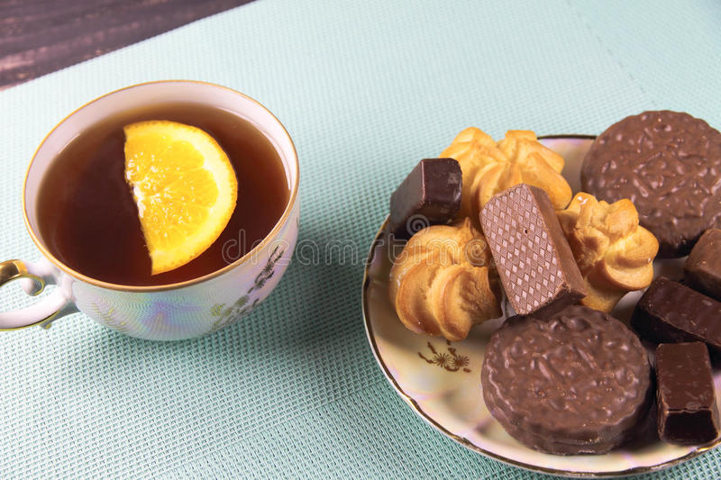 Tea and sweets on a mint background. Orange royalty free stock images