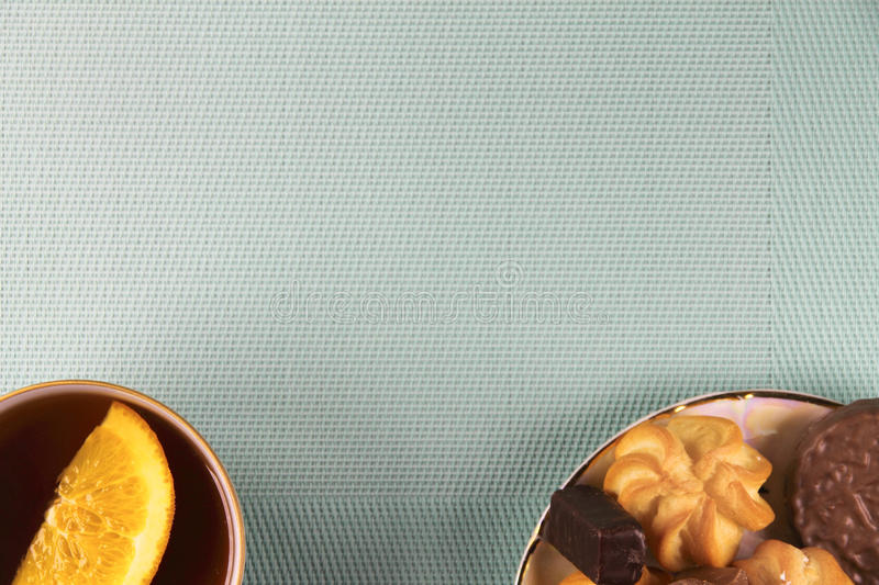 Tea and sweets on a mint background. Orange stock image