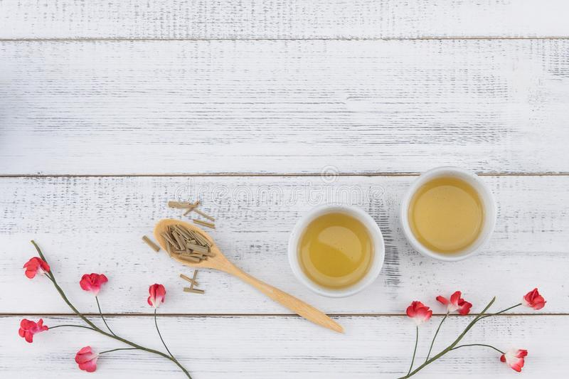 Tea and tea leaves on wooden spoon. Decorate with red paper flowers on white wood background with copy space stock images