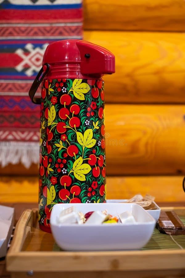 Tea thermos w rosyjskim stylu ludowym Khokhloma i cukierki na stole zdjęcie stock