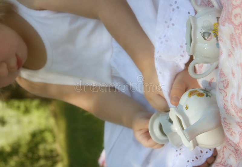 Tea Time. Soft focus, girl in background, vintage tea set in front stock photos