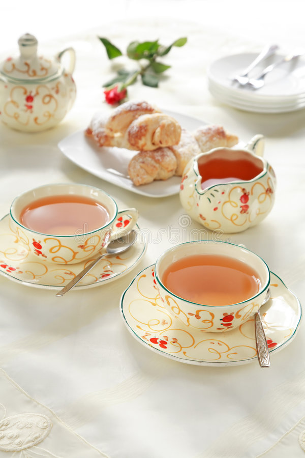 Tea time. Two cups of tea with small sweet rolls stock image