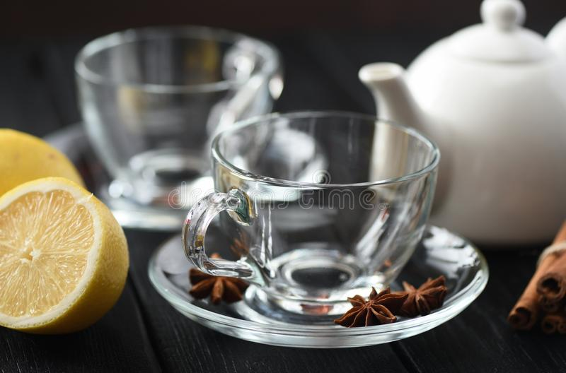 Tea time. Empty glass teacups with lemon and spices on black background stock photos